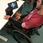 A young man sitting in a wheelchair plays with Skoog and iPad.